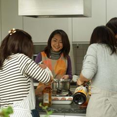 アイランドキッチンを囲んで料理中の写真